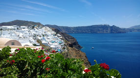 Piękny jaskrawy panoramiczny widok Oia w Santorini biali budynki jaskrawy morze i piękne rośliny w przedpolu -, Obraz Royalty Free