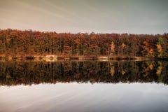 Piękny jezioro i kolorowy las w jesień wieczór zaświecamy Piękny las kolorowi jesieni drzewa odbija w spokojnym jeziorze w d Fotografia Royalty Free