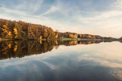 Piękny jezioro i kolorowy las w jesień wieczór zaświecamy Piękny las kolorowi jesieni drzewa odbija w spokojnym jeziorze w d Zdjęcia Stock