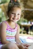 Piękny kędzierzawy z włosami młodej dziewczyny ono uśmiecha się fotografia stock