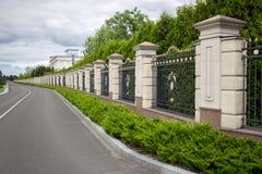 Piękny kamienia ogrodzenie z forged metal bramami malował z złotem Obrazy Royalty Free