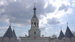 Piękny kościół na tle chmury i słońce, dzwonnik dzwoni dzwon na kościelny dzwonkowy wierza, a zdjęcie wideo