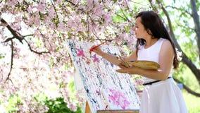 Piękny kobieta malarz w biel sukni, artysta maluje obrazek kwiaty w kwitnącej wiosny jabłczanym sadzie, ona trzyma zdjęcie wideo