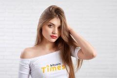 Piękny kobieta model w białym uprawa wierzchołku z bitcoin logem pozuje kamera fotografia royalty free