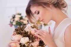 piękny kobieta model z świeżym dziennym makeup i romantyczną falistą fryzurą trzyma bukiet kwiaty, fotografia stock