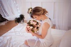 piękny kobieta model z świeżym dziennym makeup i romantyczną falistą fryzurą trzyma bukiet kwiaty, zdjęcie stock