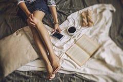 Piękny kobieta model z kawą, ciasta, domowy telefon na b Obrazy Stock