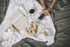 Piękny kobieta model z kawą, ciasta, domowy telefon na b Fotografia Royalty Free