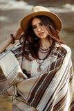 Piękny kobieta modnisia portret, trzymający kapelusz i poncho, elegancki strój, boho podróży pojęcie, zmysłowy spojrzenie Fotografia Royalty Free
