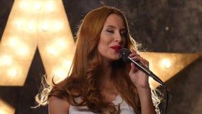 Piękny kobieta piosenkarz z mikrofonem, błyszczy zbiory wideo