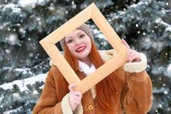 Piękny kobieta portret na zimie plenerowej, spojrzenie przez drewnianej ramy, śnieżni jedlinowi drzewa w lesie, długi czerwony wł Zdjęcie Royalty Free