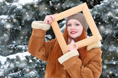 Piękny kobieta portret na zimie plenerowej, spojrzenie przez drewnianej ramy, śnieżni jedlinowi drzewa w lesie, długi czerwony wł Zdjęcia Royalty Free