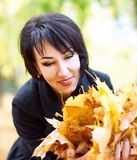 Piękny kobieta portret z garścią liście w jesieni plenerowej, kolorów żółtych liście i drzewa na tle, sezon jesienny Zdjęcia Royalty Free