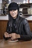 Piękny kobieta tekst podczas gdy pijący jej kawę Zdjęcia Stock