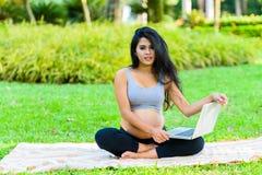 Piękny kobieta w ciąży joga z laptopem Obraz Royalty Free