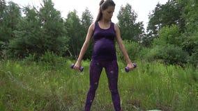 Piękny kobieta w ciąży robi sportowi w lato parku zbiory wideo
