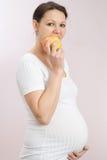 Piękny kobieta w ciąży stoi jabłka i je obrazy stock