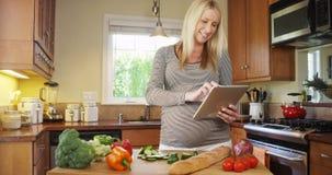 Piękny kobieta w ciąży używa pastylkę w kuchni Obraz Stock