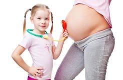 Piękny kobieta w ciąży z jej córką. zdjęcia royalty free
