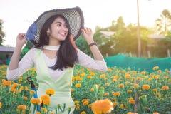Piękny kobiety Asia styl na żółtym kwiatu ogródzie i patrzeć sm fotografia royalty free