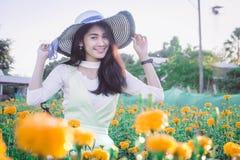 Piękny kobiety Asia styl na żółtym kwiatu ogródzie i patrzeć sm fotografia stock