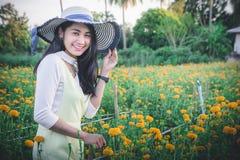 Piękny kobiety Asia styl na żółtym kwiatu ogródzie i patrzeć sm obrazy royalty free