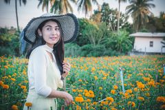 Piękny kobiety Asia styl na żółtym kwiatu ogródzie i patrzeć sm zdjęcie royalty free