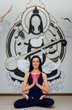 Piękny kobiety joga trenera obsiadanie w lotosowej pozycji na tle obrazek Indiańska bogini Zdrowy styl ?ycia, fotografia royalty free