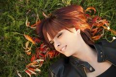 Piękny kobiety lying on the beach na jesień liściach Fotografia Stock