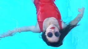 Piękny kobiety lying on the beach na wody powierzchni, relaksuje w basenie na wakacje zbiory wideo