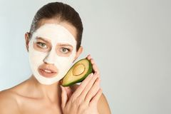Piękny kobiety mienia avocado blisko jej twarzy z gliny maską przeciw popielatemu tłu obrazy royalty free