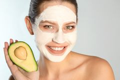 Piękny kobiety mienia avocado blisko jej twarzy z gliny maską przeciw popielatemu tłu fotografia stock