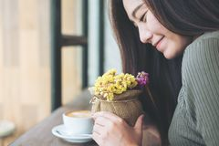 Piękny kobiety mienie i wąchać kwiaty z czuć szczęśliwy w rocznik drewnianej kawiarni z plamy filiżanką zdjęcia royalty free