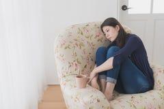 Piękny kobiety obsiadanie na żywej izbowej kanapie Zdjęcie Stock