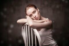 Piękny kobiety obsiadanie na białym krześle obraz stock