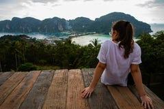 Piękny kobiety obsiadanie na drewnianej platformie z Phi Phi wyspy widokami i chmurnym niebem obraz stock