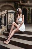 Piękny kobiety obsiadanie na starych schodkach przy kasztelem zdjęcia royalty free