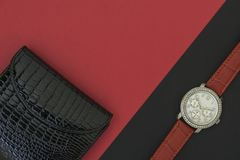 Piękny kobiety wristwatch na czarnym tle Piękny murzynka portfel na czerwonym tle obrazy stock