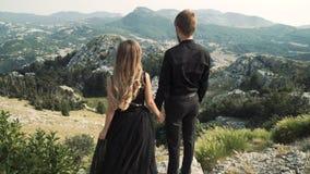 Piękny kochający pary młodej kobiety model w mądrze długiej sukni i mężczyzna w czarnym kostiumu pozuje na kamerze przeciw a zbiory