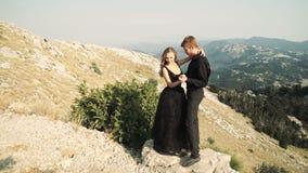 Piękny kochający pary młodej kobiety model w mądrze długiej sukni i mężczyzna w czarnym kostiumu pozuje na kamerze przeciw a zbiory wideo