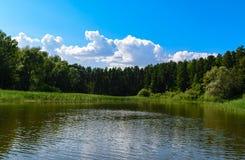 Piękny krajobraz z niebieskiego nieba i bielu chmurami odbijał w jasnej wodzie rzecznej idylliczny lato fotografia royalty free