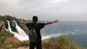 Piękny krajobrazowy widok natura, siklawa i morze, Turystów stojaki na skłonie z jego rękami szeroko rozpościerać zbiory