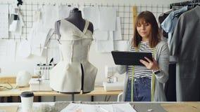 Piękny krawczyna obraca krawiectwo atrapy sprawdzać przypiętą odzież i działanie z pastylką wchodzić do informację używać zbiory