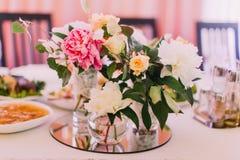 Piękny kwitnący bukiet colourful peonie w wazach na ślubu stołu secie i róże Obrazy Stock