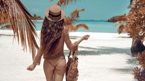 Piękny luksusu schudnięcie z powrotem brunetki kobieta w beżowym swimsuit pozuje ocean wodą Seksowny garbnikujący ciało, do obrazy royalty free
