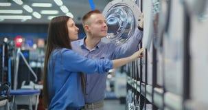 Piękny mężczyzna i kobieta wybieramy nowożytną mądrze pralkę w elektronika użytkowa sklepie dla ich nowego nowożytnego d zbiory wideo