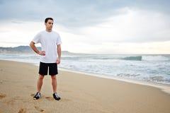Piękny męski biegacz odpoczywa po intensywnego ranku jogging stać na plaży ubierał w białej koszulce Fotografia Royalty Free