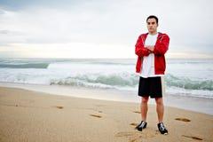 Piękny męski biegacz z krzyżującą ręk spoczynkową pozycją na piasku na fala tle Obrazy Royalty Free