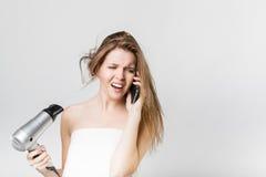 Piękny młoda dziewczyna cios suszy jej włosy podczas gdy opowiadający na s Zdjęcie Royalty Free