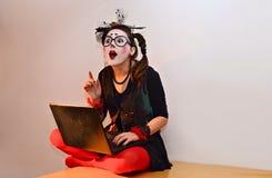 Piękny młoda dziewczyna mim, dostawać doskonałego pomysł blisko laptopu Obrazy Royalty Free